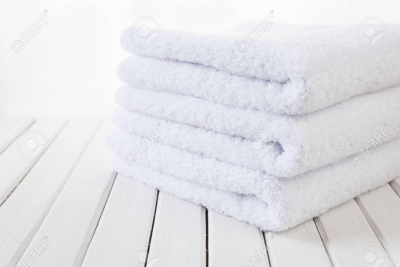 Una pila di tre asciugamani da bagno soffici bianchi sullo sfondo di
