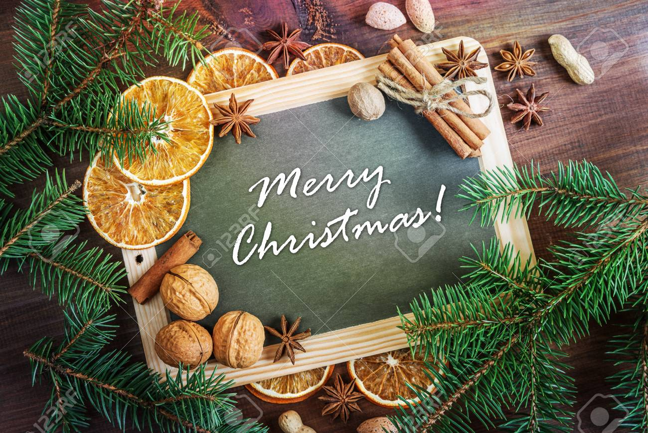 Carte de voeux de Noël: tableau avec inscription Joyeux Noël! entouré de  branches de sapin vert, de noix, d\'oranges et d\'épices