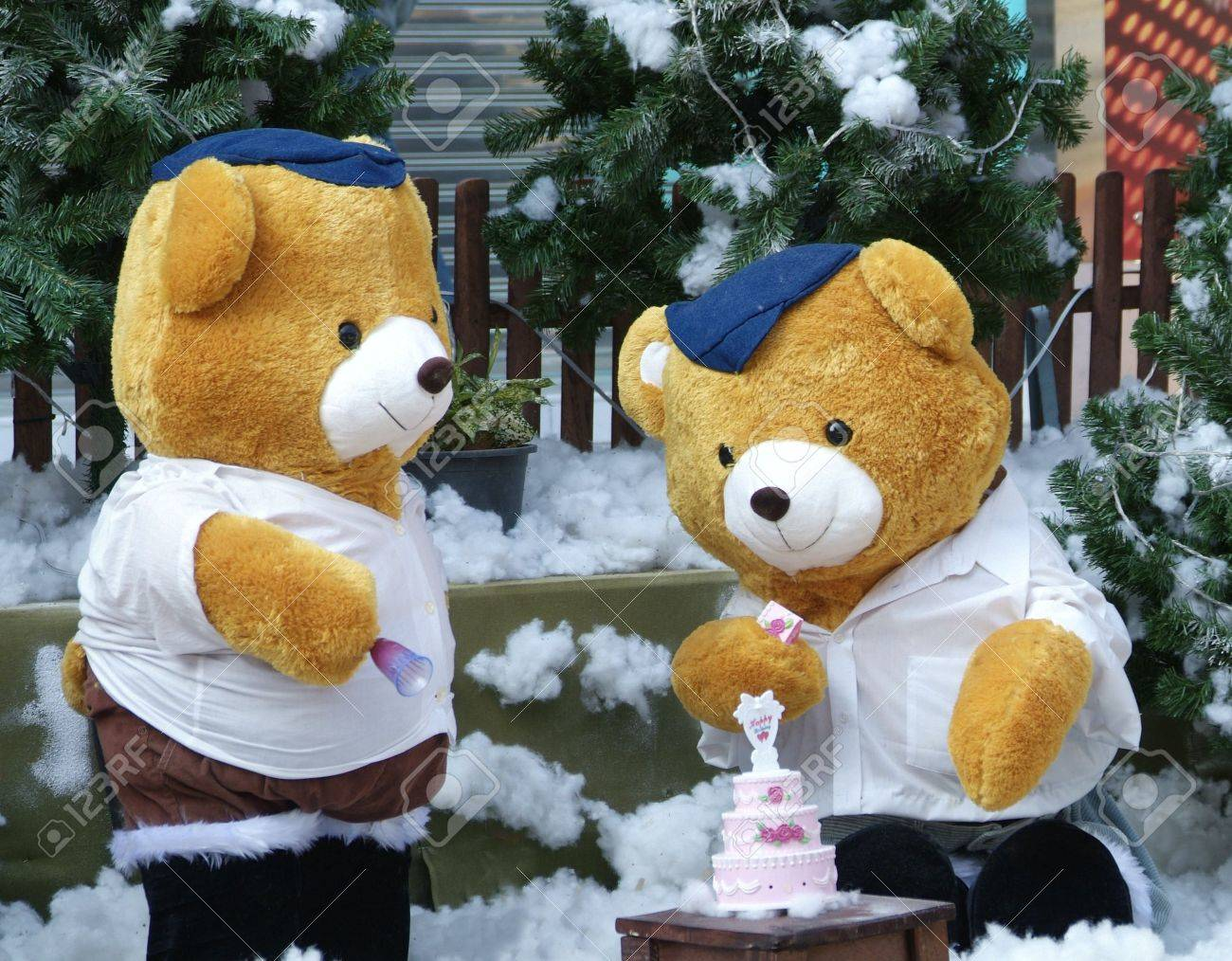 teddy bears having a birthday celebration with a pink cake in