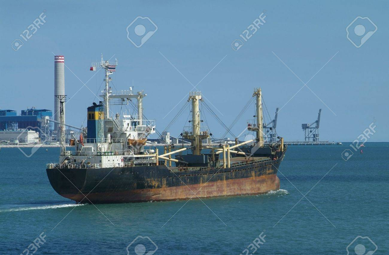 Old, rusty freight ship leaving a tropical, industrial harbour