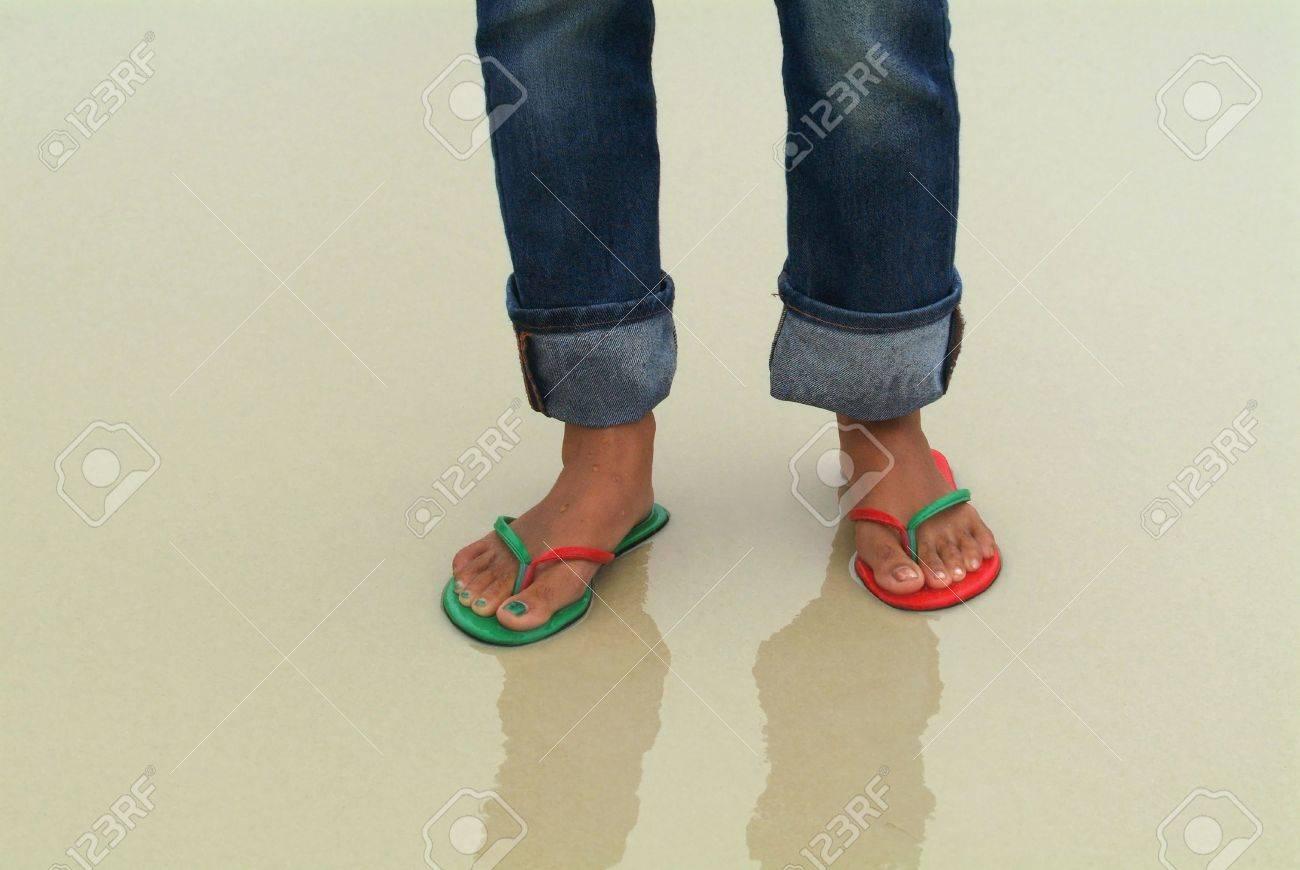 Los pies de una mujer en una playa húmeda. El pie derecho lleva una sandalia verde, el rojo y el pie izquierdo, con las uñas de los pies pintadas de colores coincidentes, y que corresponden a los colores de las lámparas de barco.  Foto de archivo - 898911