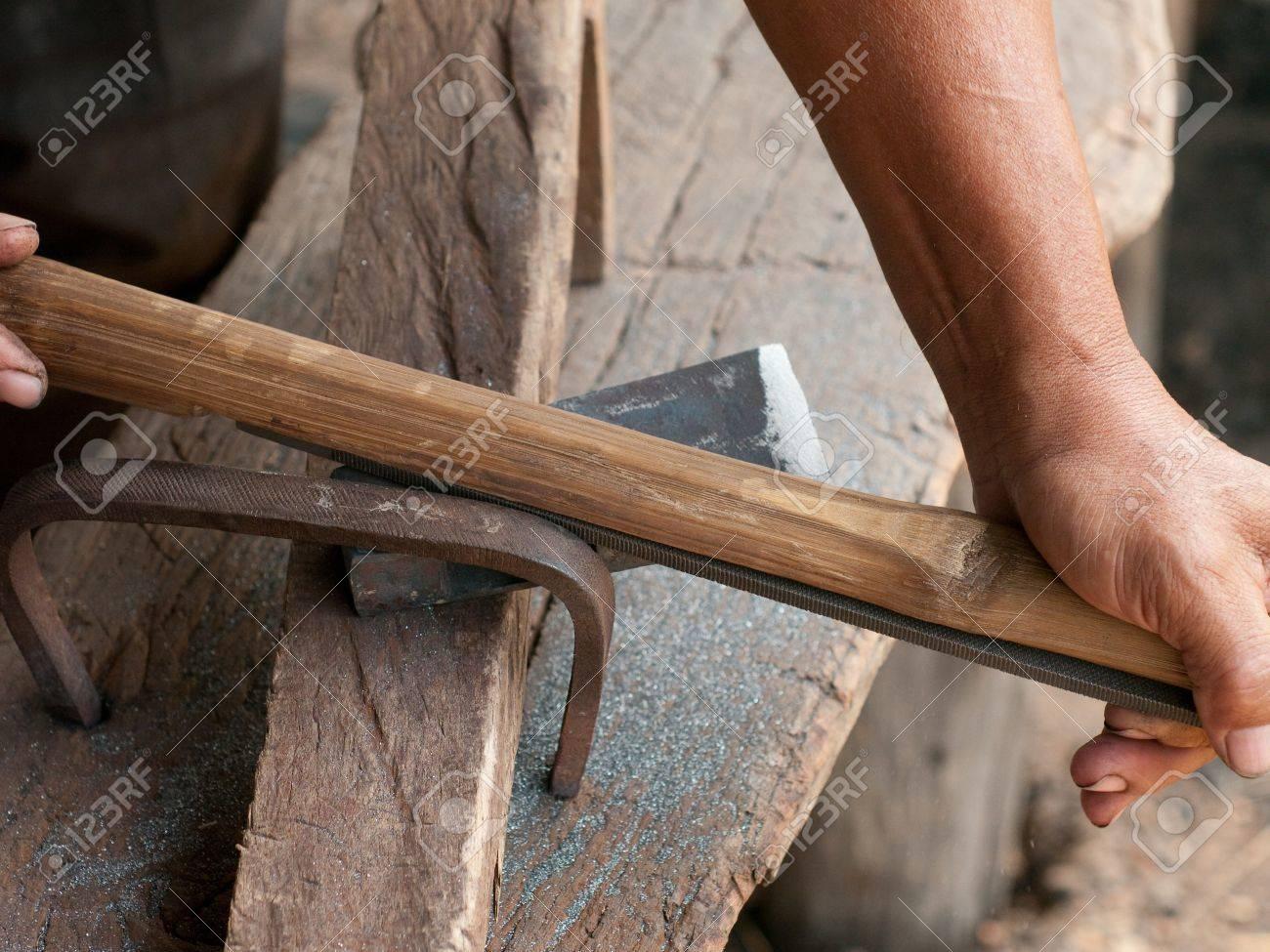blacksmith schärfen eine axt, die eine datei auf einer welle