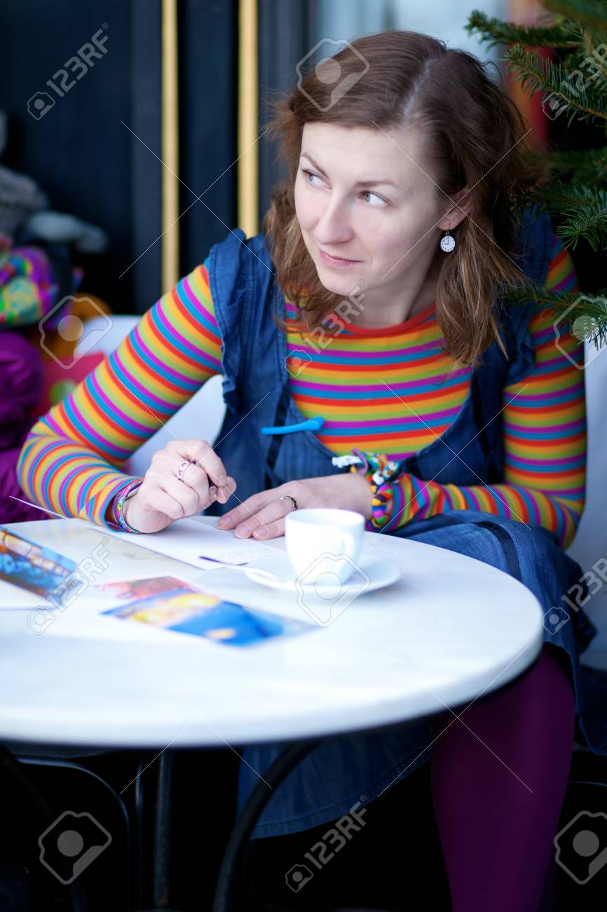 Beautiful girl in bright clothes writing postcards in cafe Stock Photo - 10410826