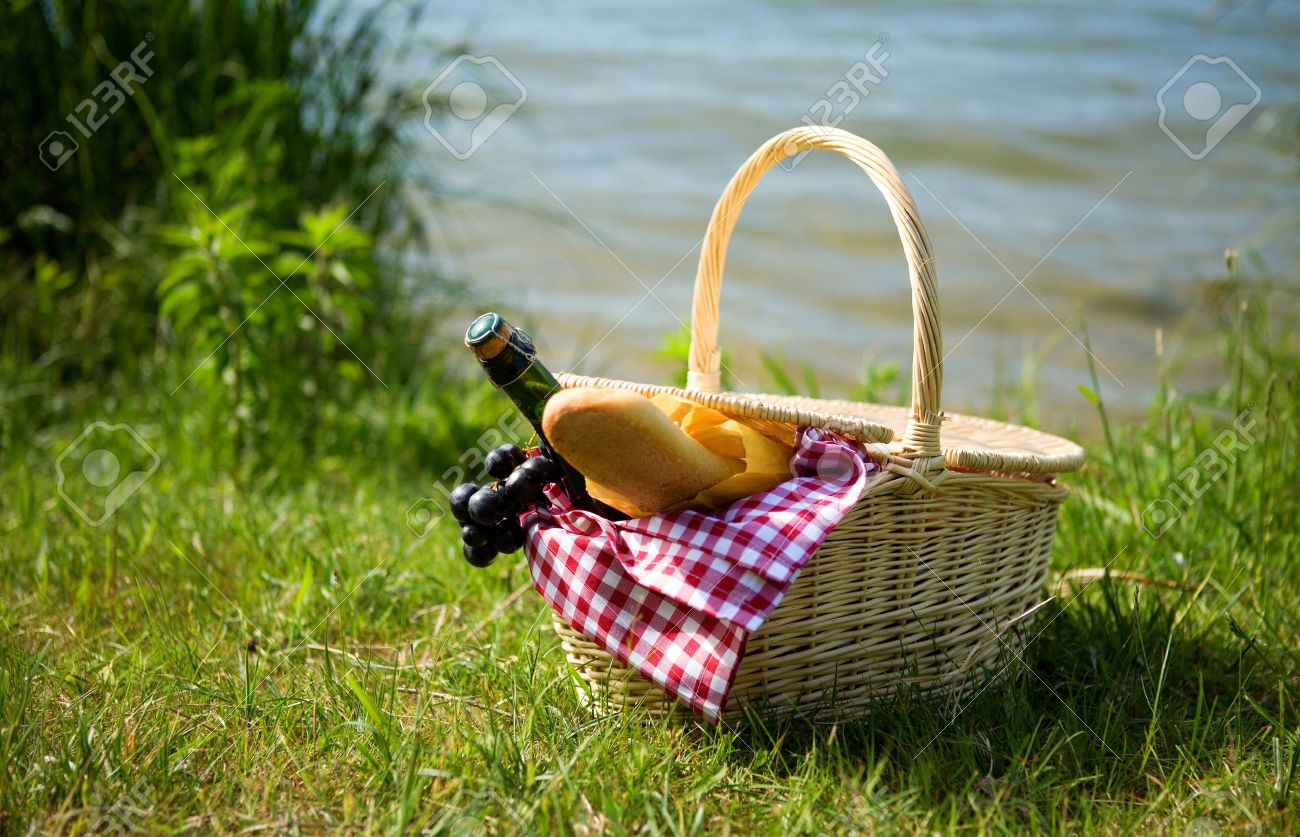 Picnic basket with food and cider bottle near the water Stock Photo - 10410930