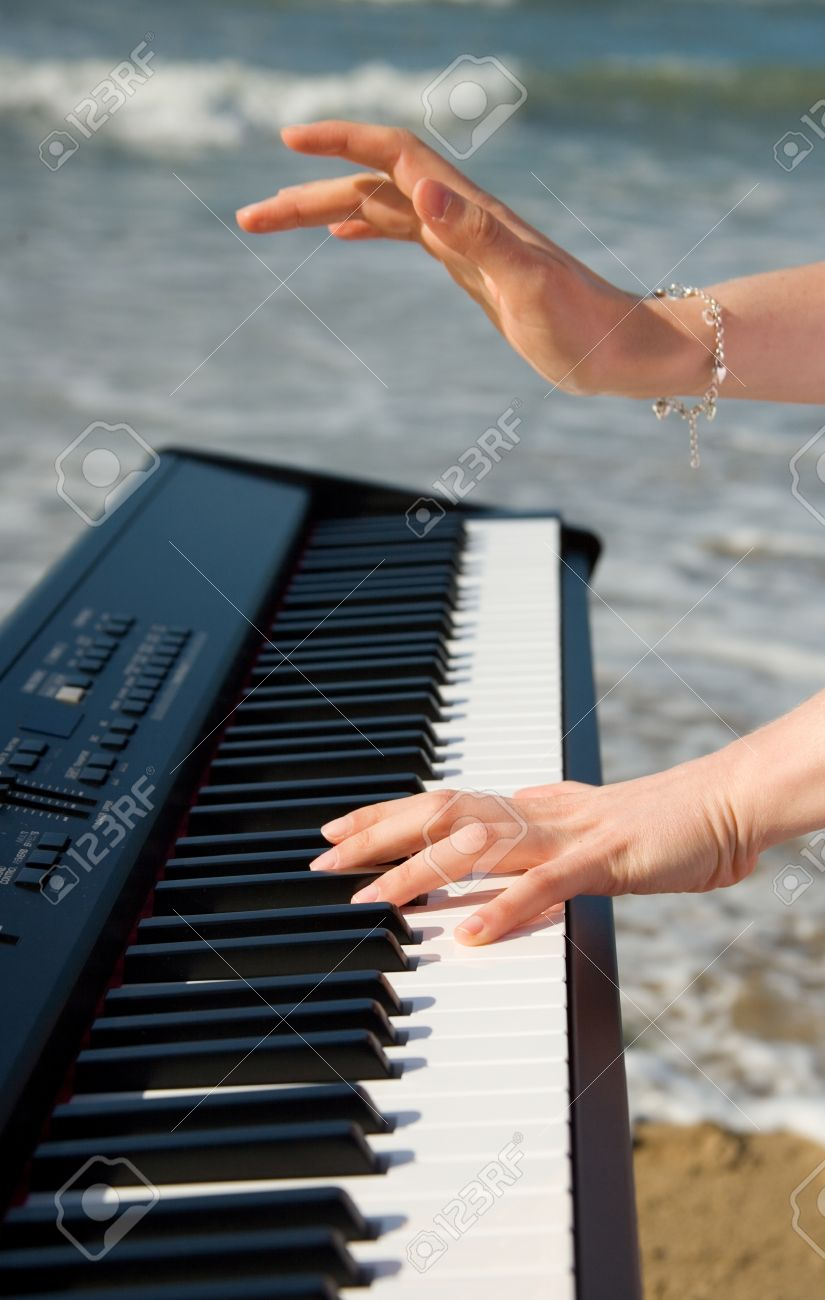 Playing music at the seashore. Beautiful female hands, piano keyboard and ocean or sea in the background Stock Photo - 10410880