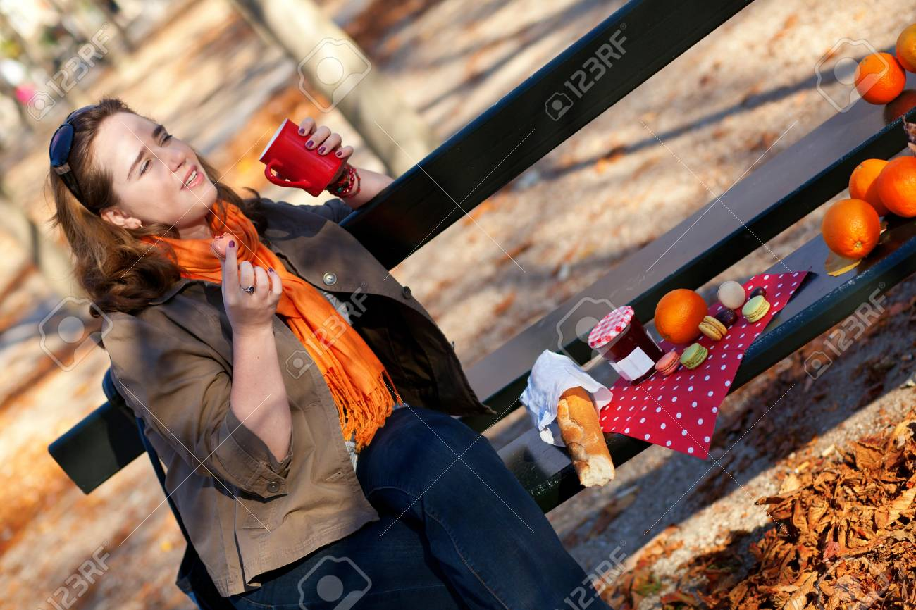 Beautiful young girl drinking hot tea in park at fall Stock Photo - 10918048