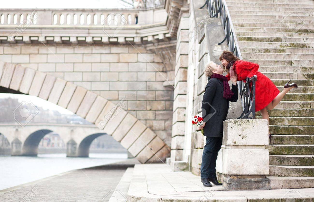 Beautiful romantic couple kissing on a Parisian embankment at spring or winter Stock Photo - 12827595