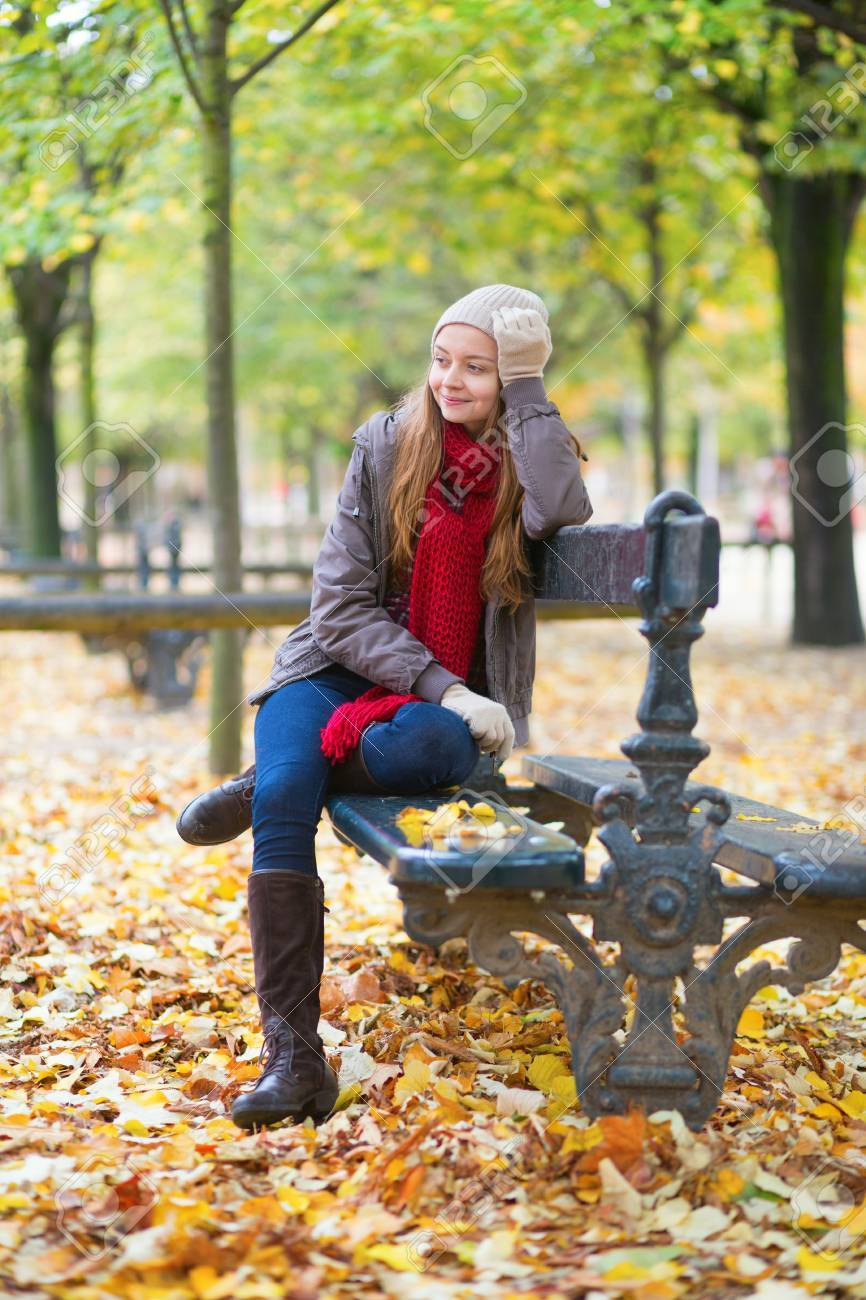 Young girl sitting on a bench in park on a fall day Stock Photo - 30082024