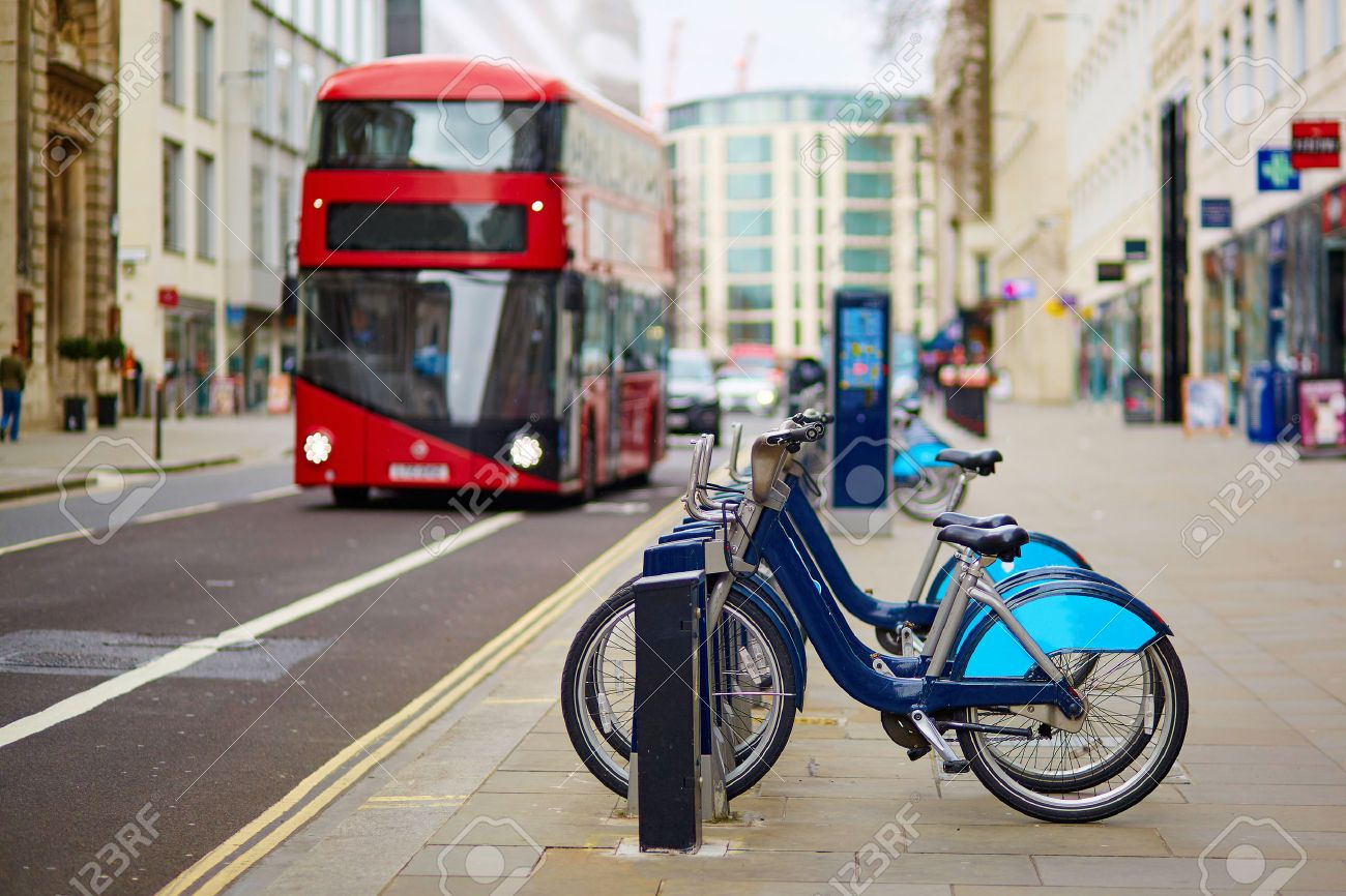 Row of bicycles for rent with red double-decker bus in the background on a street of London, UK Stock Photo - 39781525