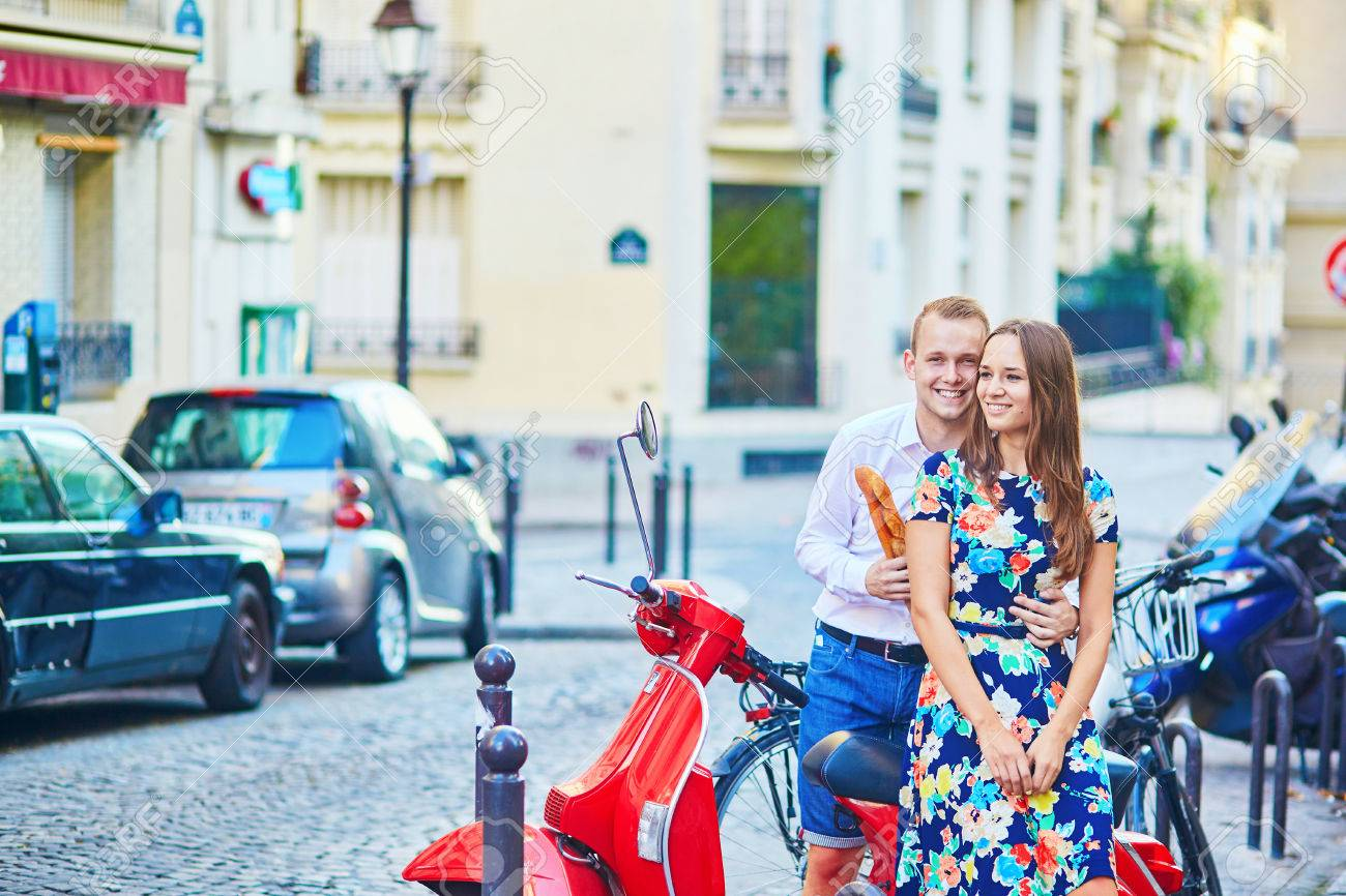 Romantic Couple With A Red Scooter Girl Is Holding A Baguette