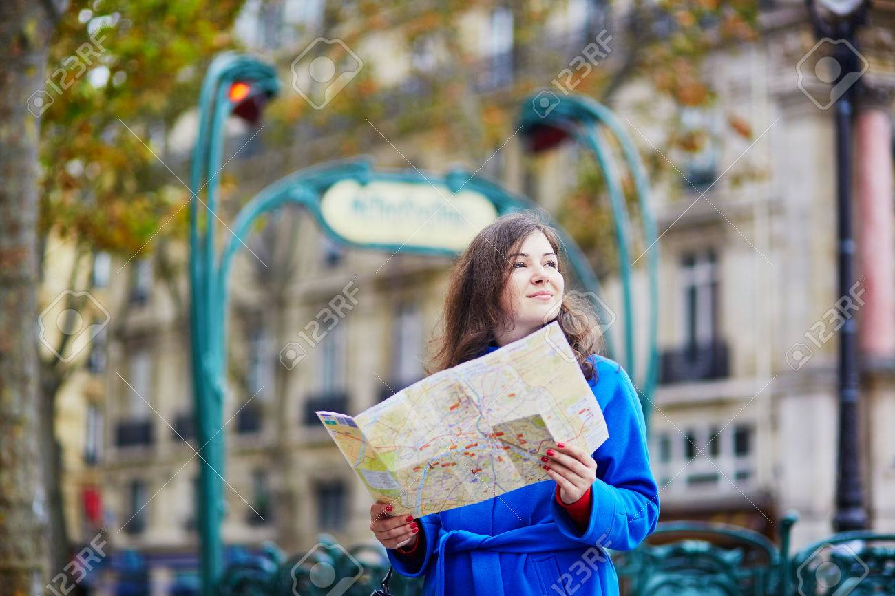 Beautiful Young Tourist In Paris Using Map Near Metro Station Stock - Paris street map with metro stations
