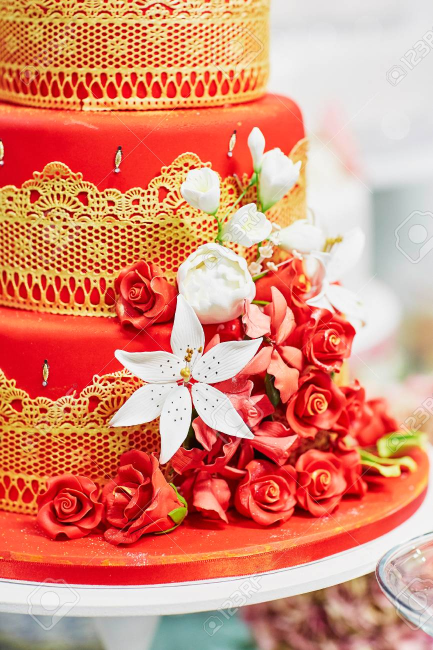 Red And Yellow Wedding Cake Decorated With Sugar Flowers And Stock