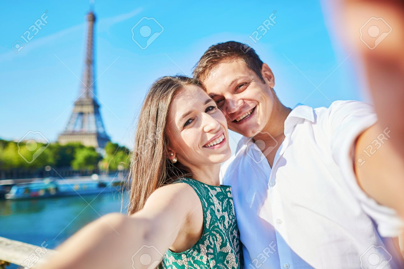Young romantic couple having a date and taking funny wide angle selfie with  mobile phone near