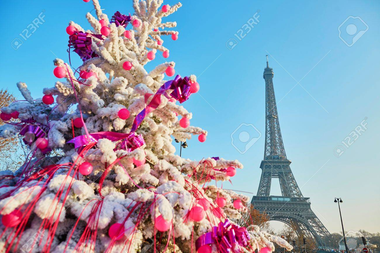 decorated christmas tree covered with snow near the eiffel tower in paris france stock photo