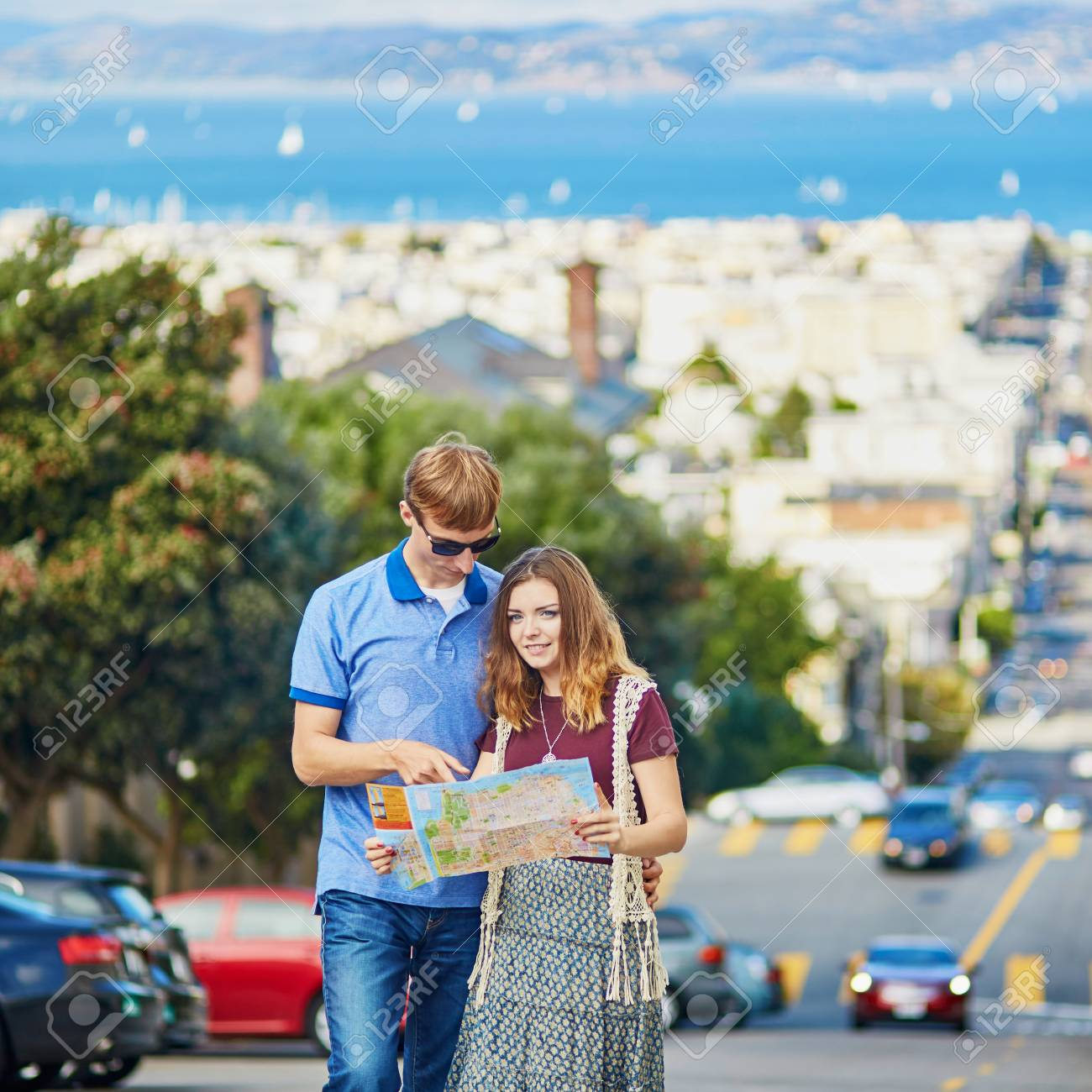 Romantic couple of tourists using map and planning their itinerary