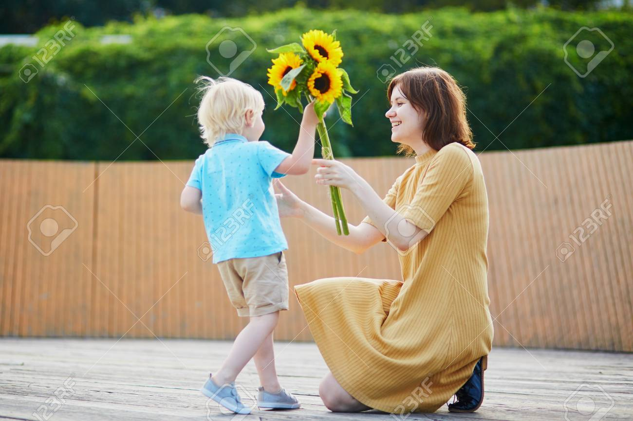 Adorable Little Boy Offering Bunch Of Sunflowers To His Mom Child Making Birthday Gift