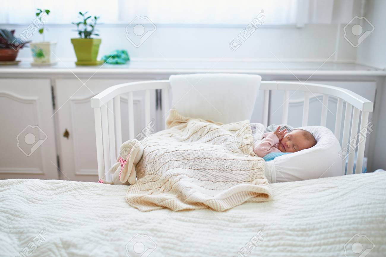 Newborn baby girl having a nap in co-sleeper crib attached to..