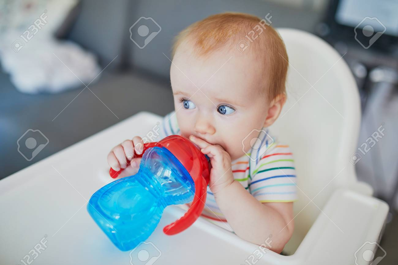 Little Baby Girl Sitting In High Chair At Home Or At Restaurant