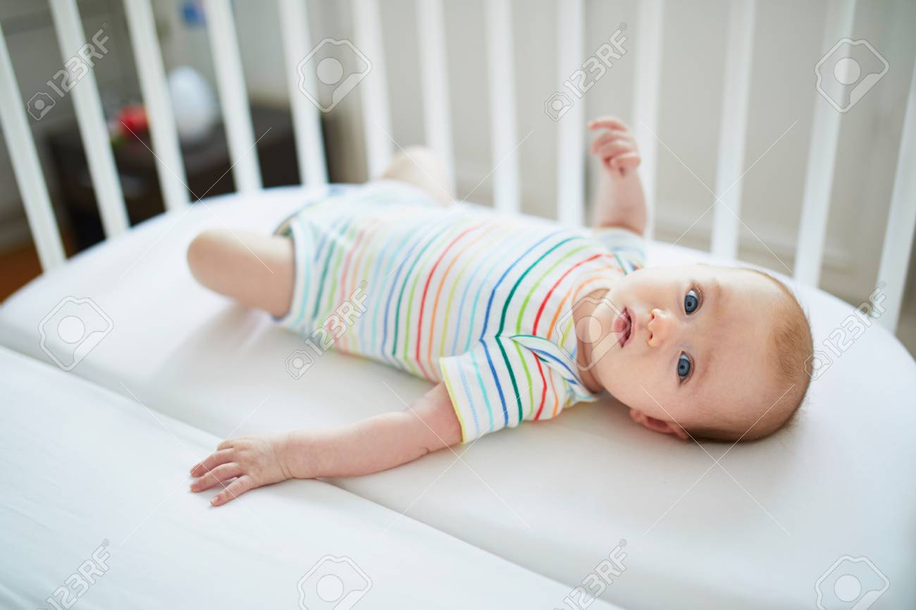 Adorable baby girl in co-sleeper crib attached to parents' bed. Little child having a day nap in cot. Infant kid in sunny nursery - 114447682