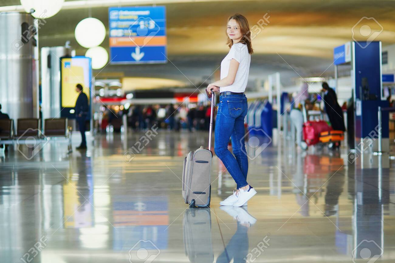 Young woman in international airport walking with luggage, ready for her flight - 122079005