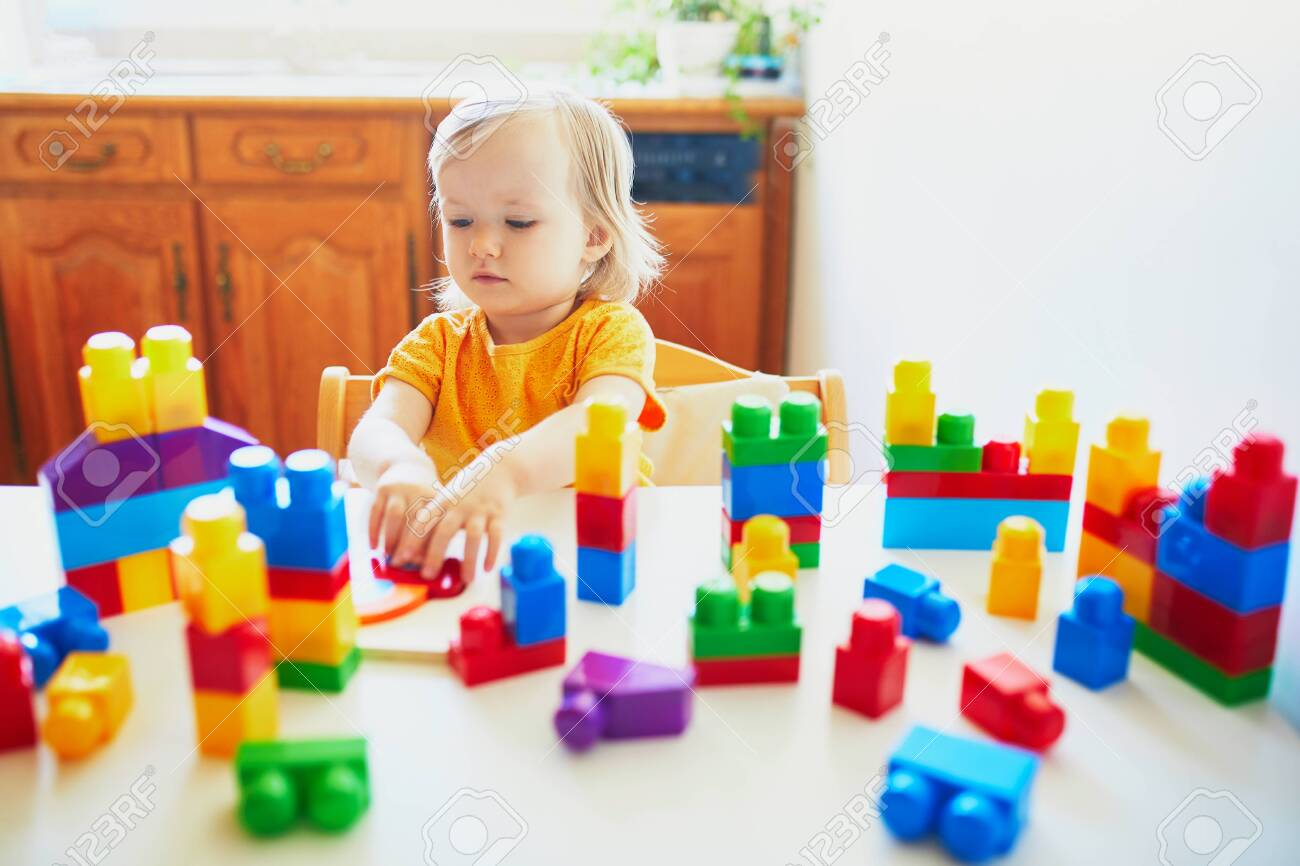 Adorable little girl playing with colorful plastic construction blocks at home, in kindergaten or preschool. Creative games for kids - 131686039