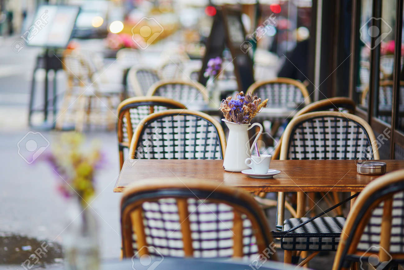 Table of traditional Parisian outdoor cafe. Cup of coffee and pitcher with dried flowers in empty restaurant in Paris, France - 156669229