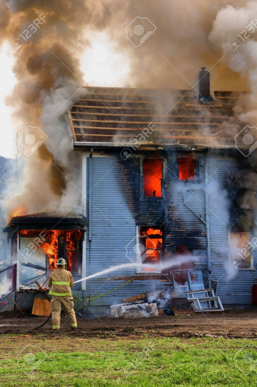 A single fireman fires his hose towarda a burning house Stock Photo - 6171768