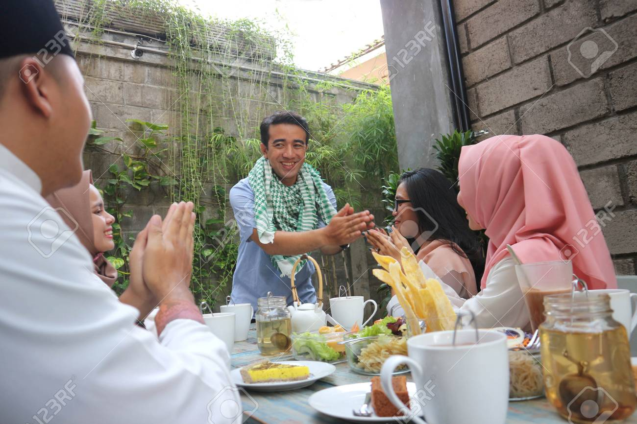 Muslim Man And Woman Having Greeting At Dining Table During Stock