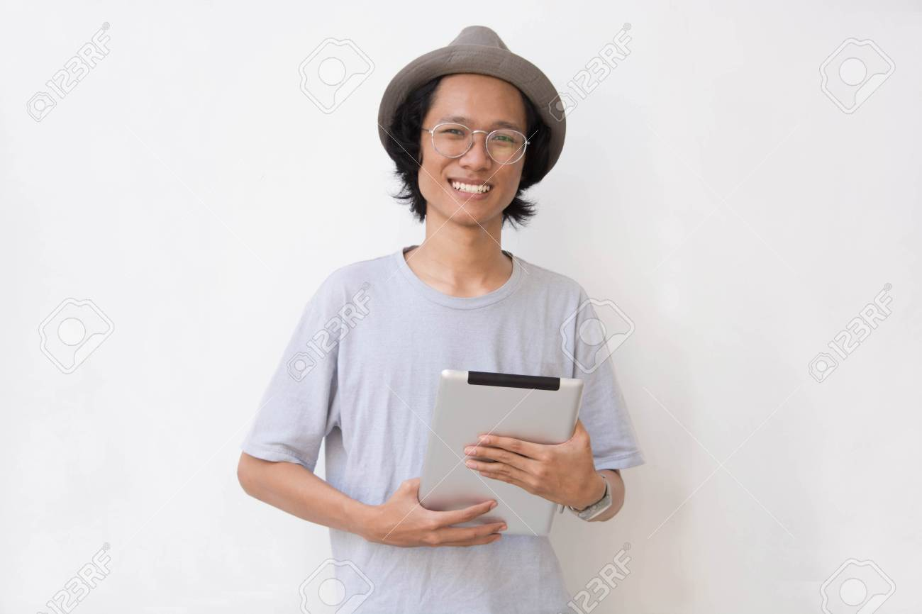 9912c09e0b07d Stock Photo - young asian man with fedora hat and glasses using tablet and  smiling