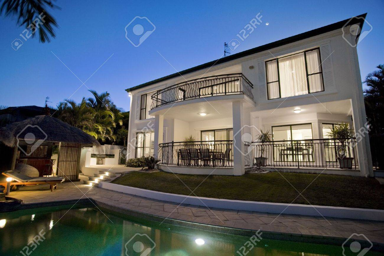 Luxurious mansion exterior at dusk overlooking pool Stock Photo - 6151949