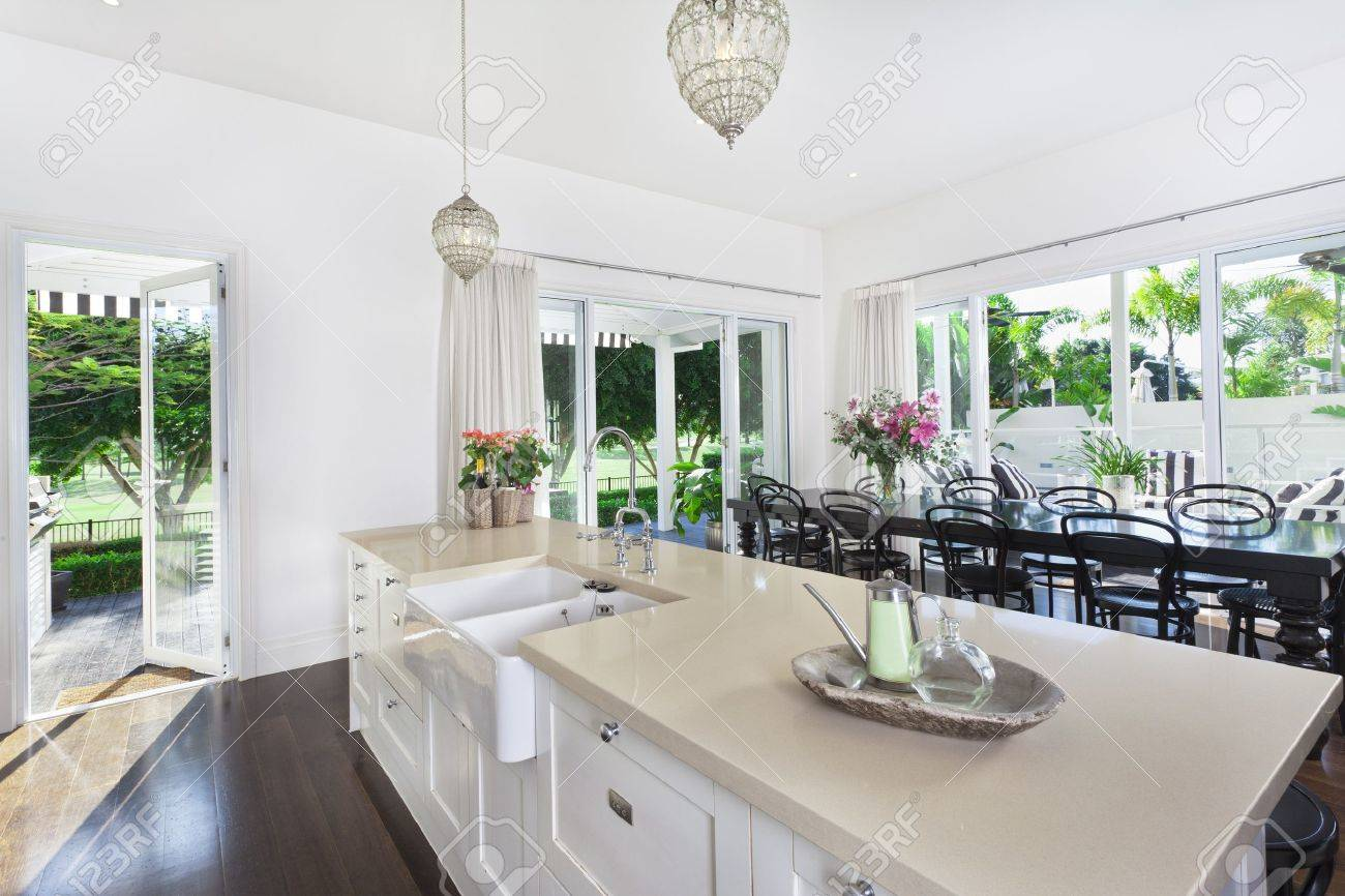 stylish open kitchen with large dining table overlooking a golf rh 123rf com