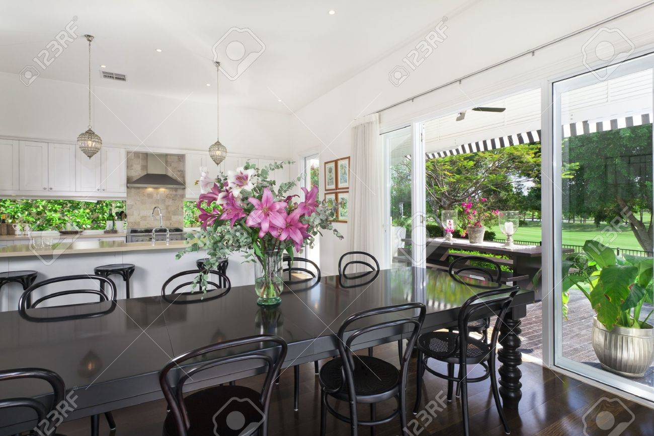 Snygg öppet kök med rostfria vitvaror och matplats med utsikt över ...