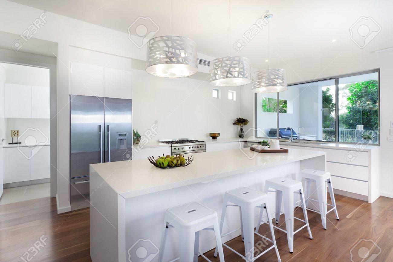 stylish open plan kitchen overlooking the backyard stock photo