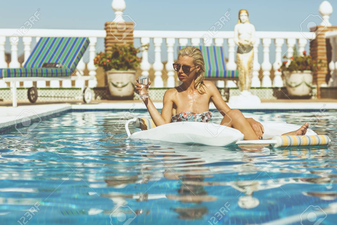 Young attractive blonde holding a glass of water and relaxing in pool on a hot summers day Stock Photo - 23067599