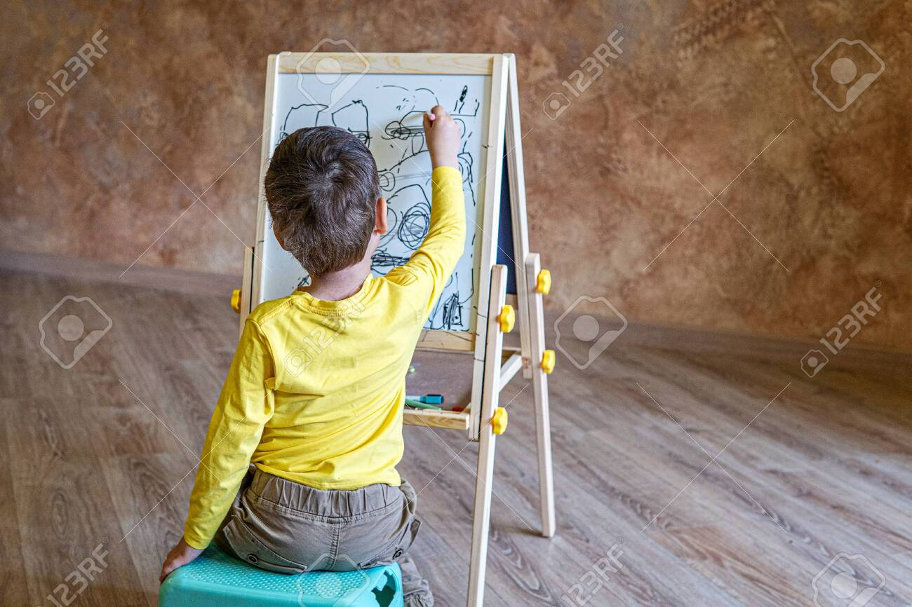 Young boy sits and drawing on drawing board with felt-tip pens - 144564909