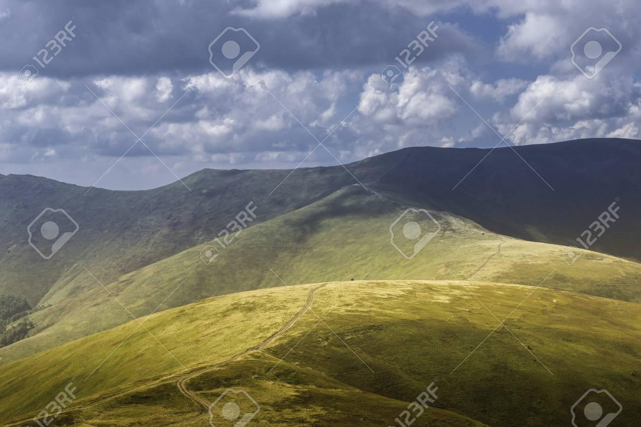 Vue d'été des Carpates et des Vallées, sous le ciel bleu avec des nuages. La route de montagne monte sur les collines sur le paysage du coucher du soleil. Banque d'images - 81867347