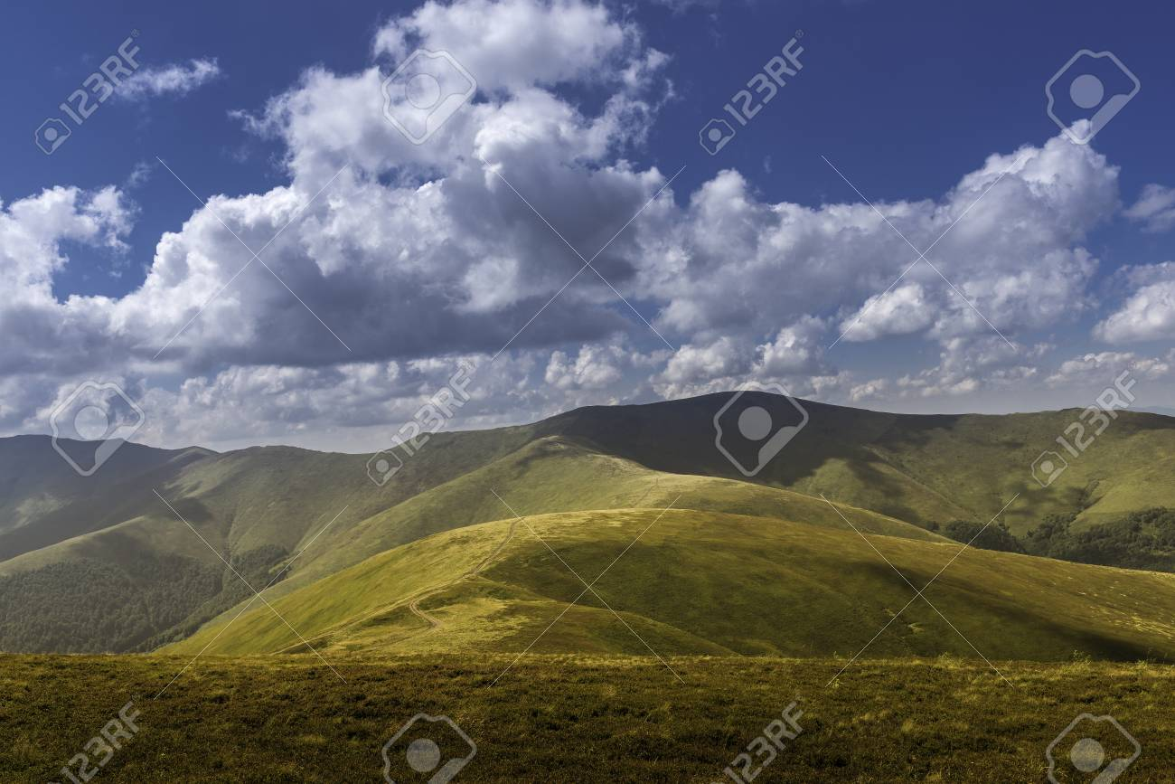 Summer view of Carpathian Mountains and Valleys, under blue sky with clouds. Mountain road goes on top of the hills on sunset landscape. Banque d'images - 81867348