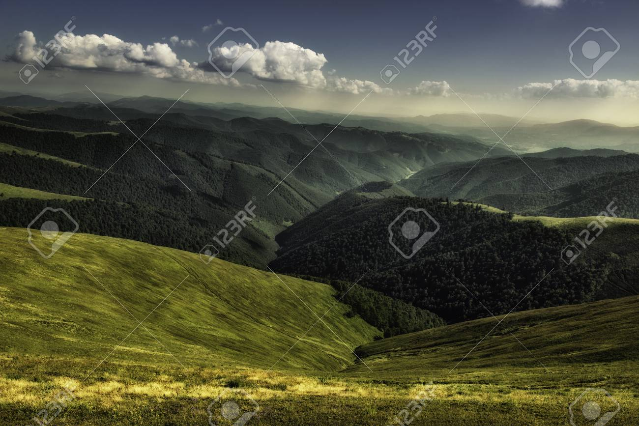 Autumn landscape. Autumn view of green Carpathian Mountains , top of the green hills on sunset landscape under blue cloudy sky. Banque d'images - 81996236