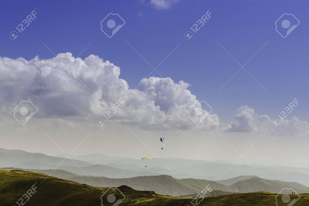 Vue d'été des Carpates et des Vallées, sous le ciel bleu avec des nuages. Avec une paire de parapentistes dans le ciel. Banque d'images - 82056127