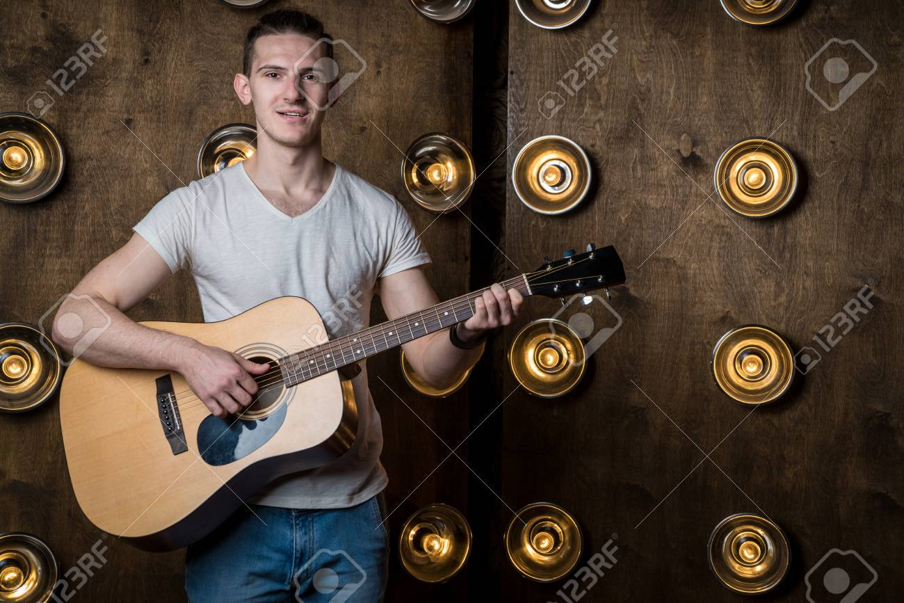 Guitarist, music  A young man plays an acoustic guitar on a background