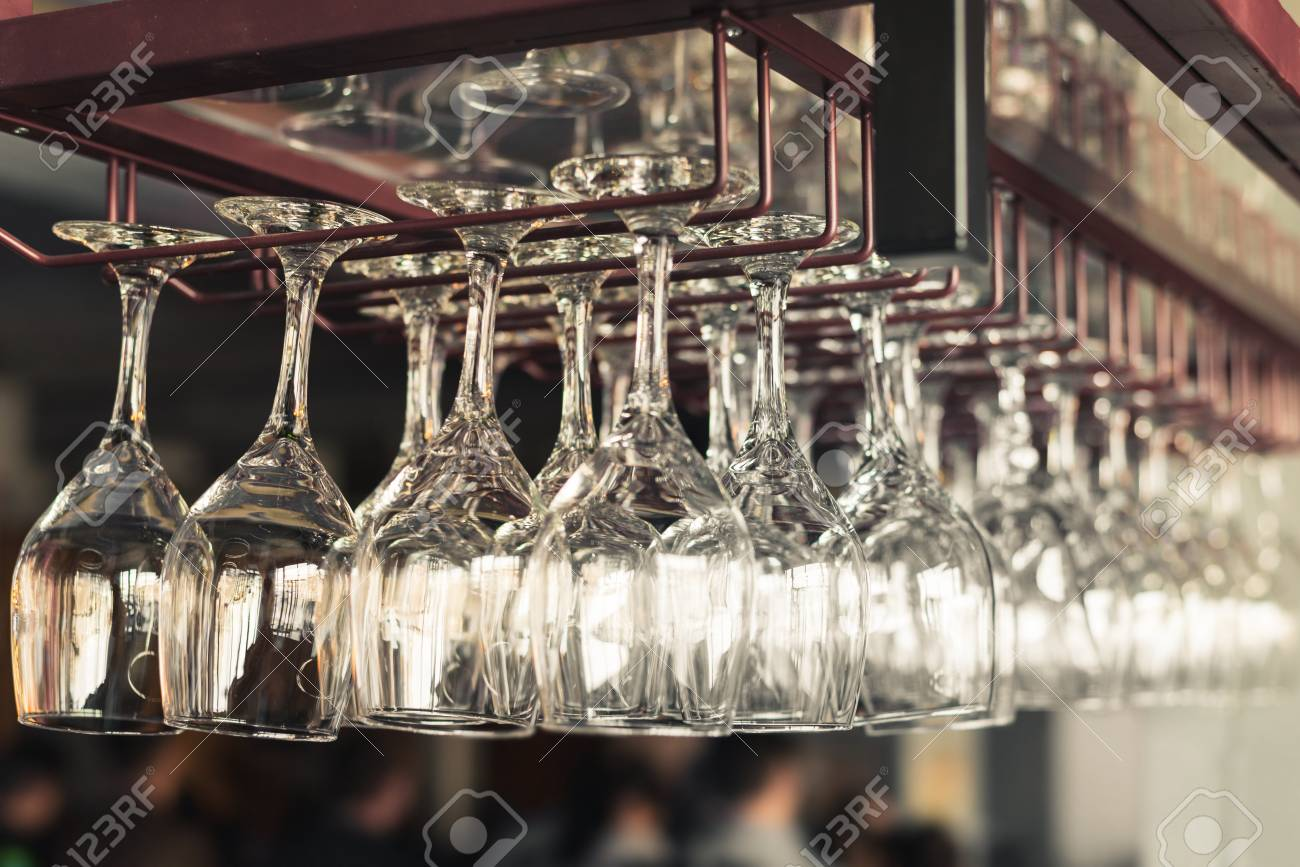A Row Of Clean Empty Wine Glasses Hang Over The Bar Counter Stock ...