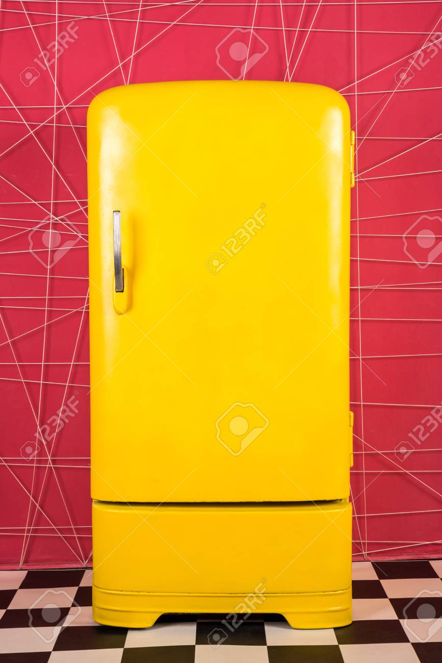 old vintage yellow refrigerator on a pink background