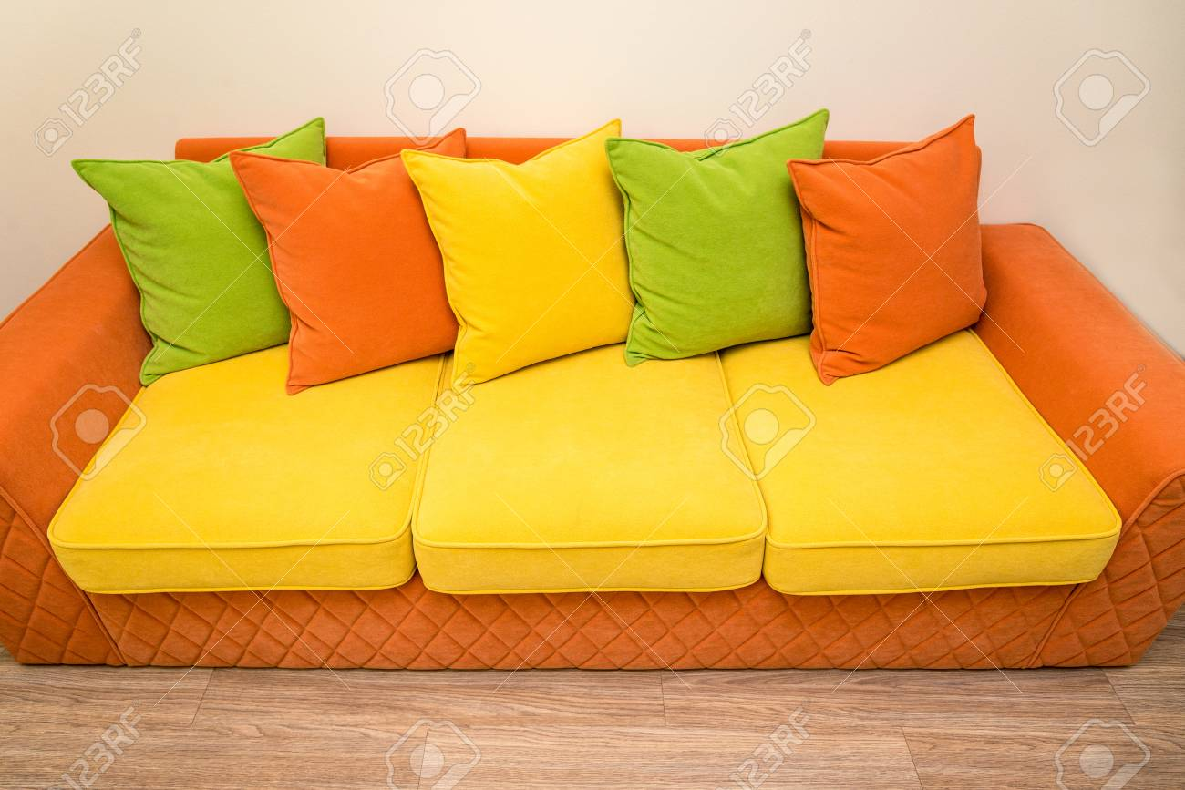a colorful yellow-orange sofa with green, yellow and orange pillows...