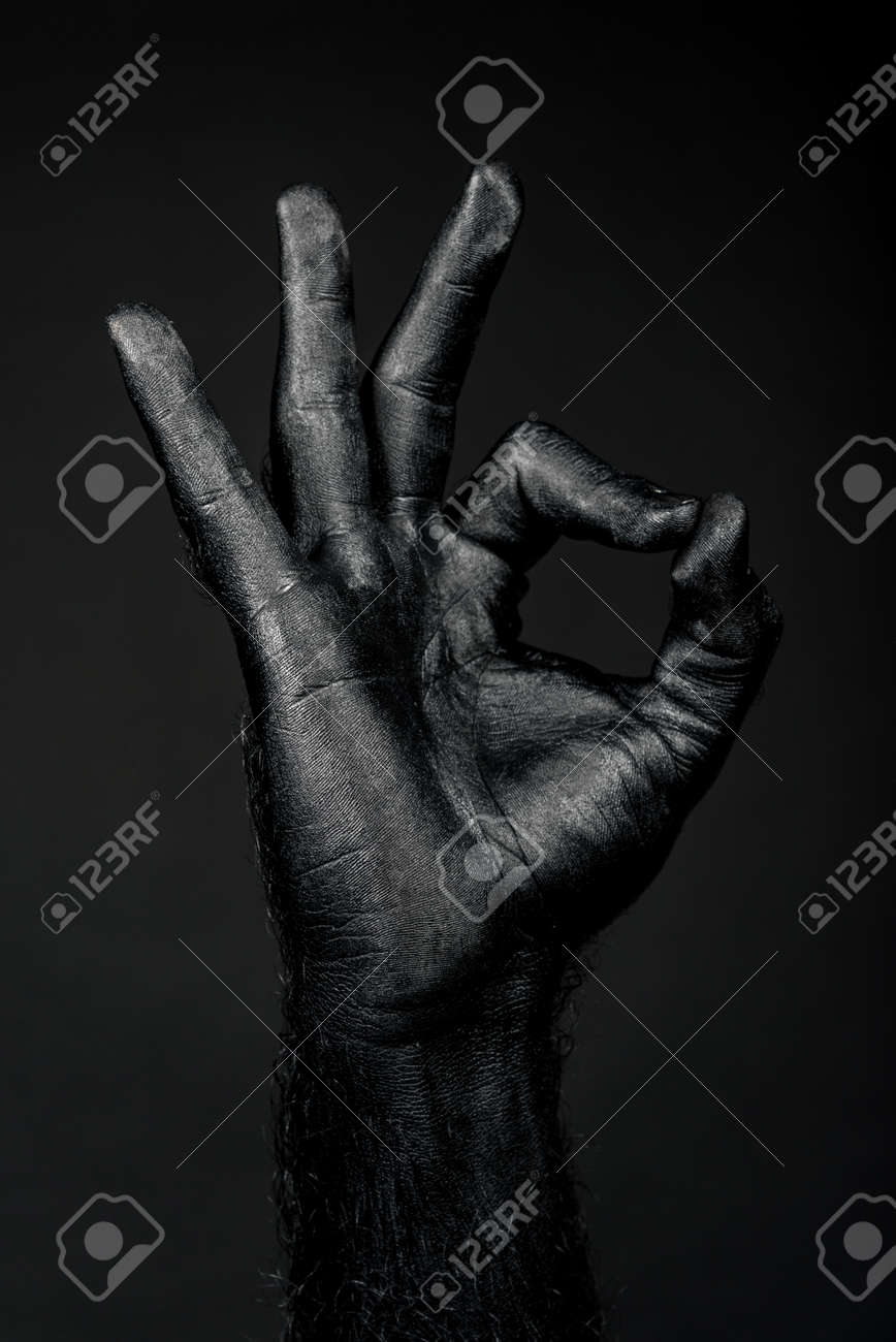 hand completely in black paint shows ok sign. Vertical frame - 121597007