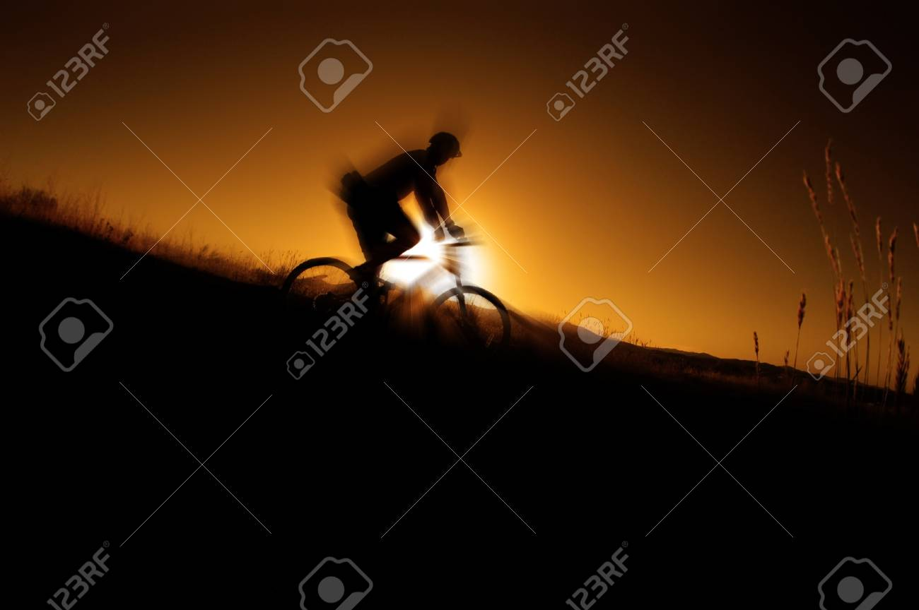 Mountain biking up a trail in the mountains with glowins sun in background Stock Photo - 9014751