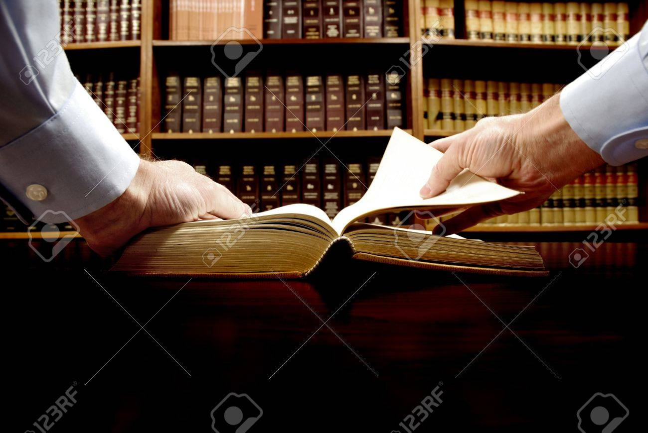 Hands holding an old book with library in background Stock Photo - 11596733