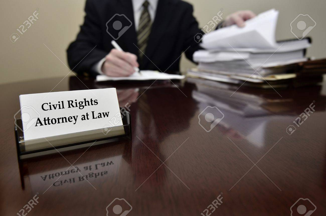 Civil Rights Attorney At Law Sitting At Desk Holding Pen With ...