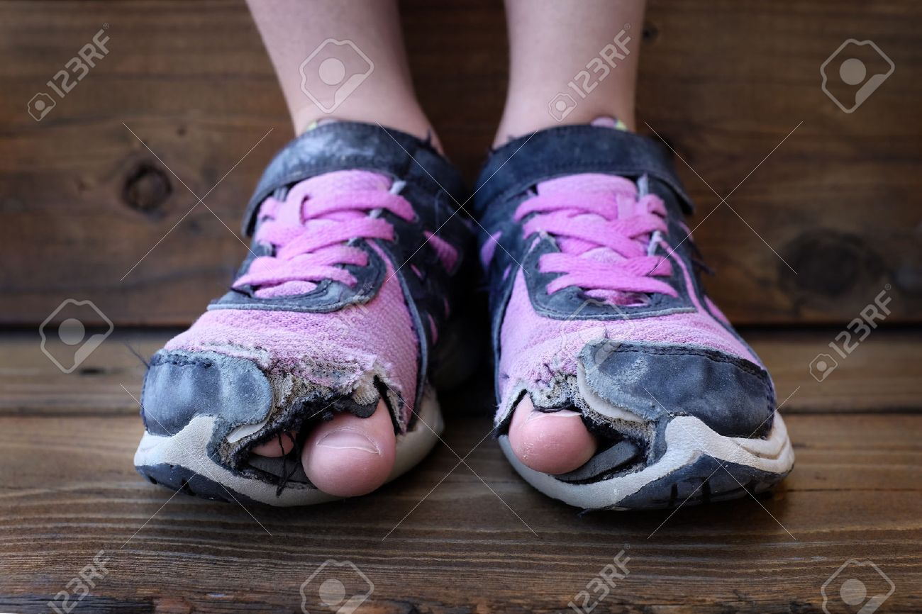 Detailed photo of shoes with holes in them and toes sticking out child kid young - 41457299