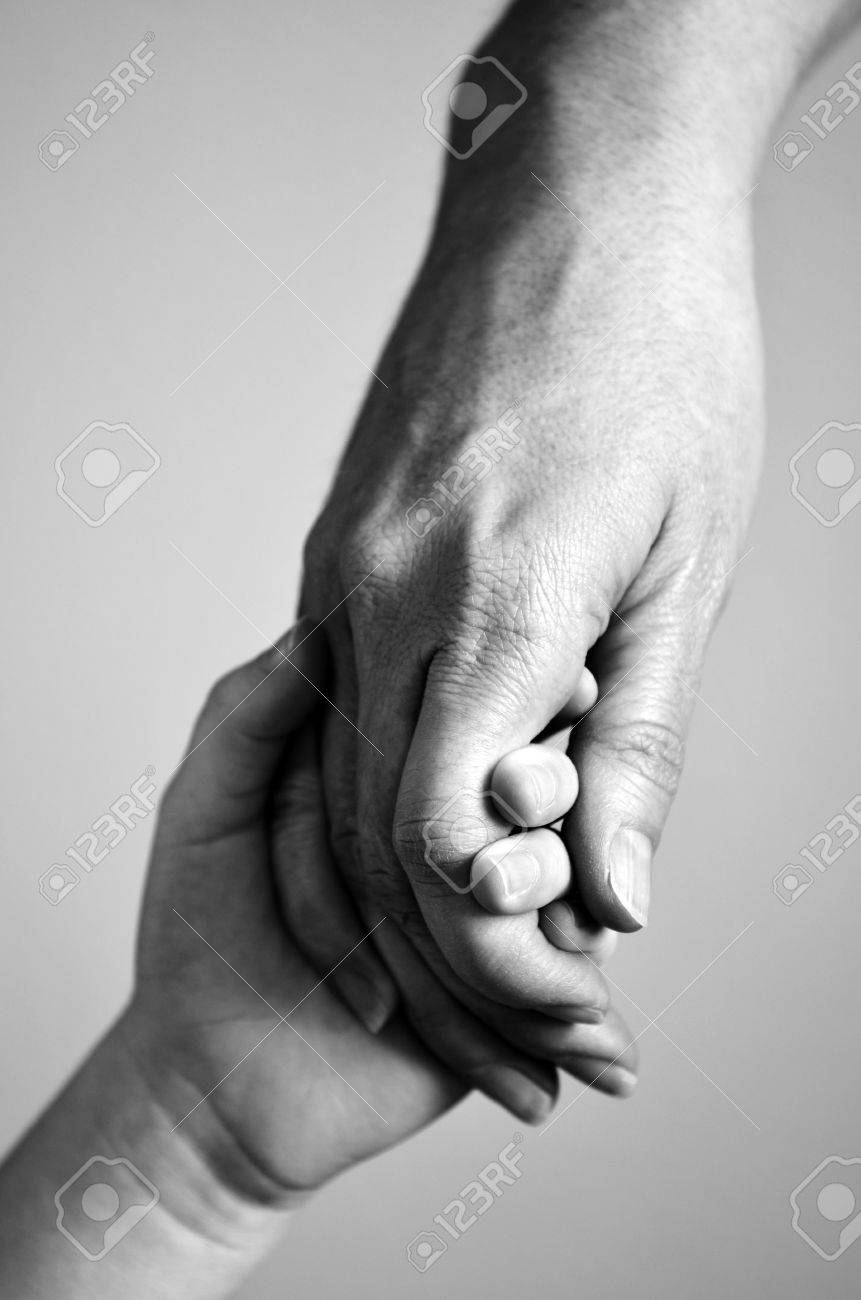 Adult or parent holding the hand of a small child - 52488285