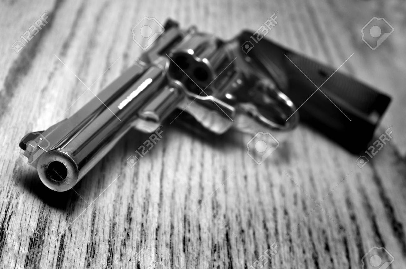 Closeup of powerful handgun with bullets on old wooden surface - 54747100
